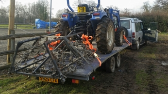Compact tractor and chain harrow loaded to tow to site.