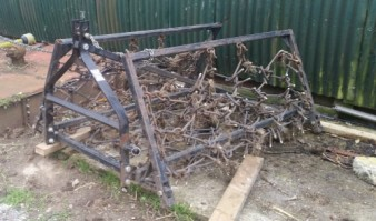 Compact tractor folding mounted chain harrow.